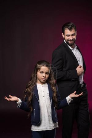 daughter showing shrug gesture on burgundy