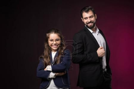 smiling daughter with crossed hands looking at camera on burgundy