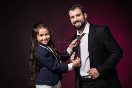 daughter fixing father tie and looking at camera on burgundy