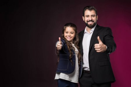 smiling father and daughter showing thumbs up on burgundy