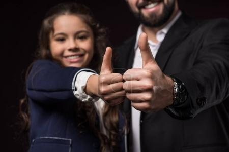 cropped image of father and daughter showing thumbs up on burgundy