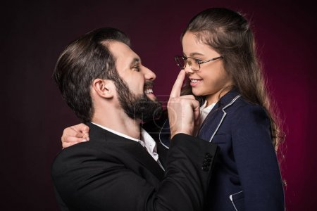 father touching daughter nose with finger on burgundy