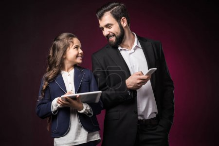 smiling father and daughter with tablet and smartphone looking at each other on burgundy