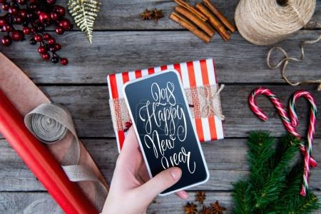 """Photo for Partial view of hand holding smartphone with """"2018 happy new year"""" lettering - Royalty Free Image"""
