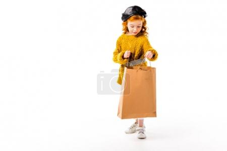 happy red hair child looking into shopping bag isolated on white