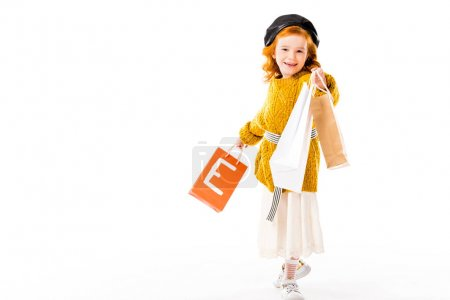 Photo for Happy red hair child showing shopping bags isolated on white - Royalty Free Image