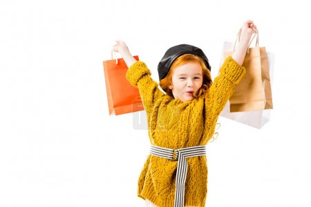 happy red hair child holding shopping bags in hands above head isolated on white