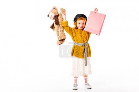Photo pour Enfant de rousse heureux holding panier et jouet dans les mains au-dessus de tête isolé sur blanc - image libre de droit