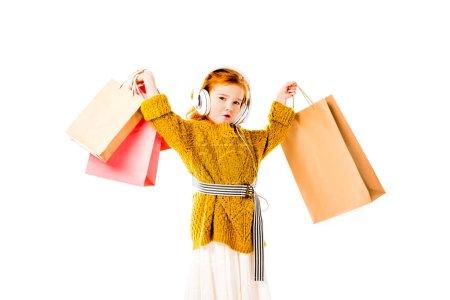 Foto de Emocionado el niño de pelo rojo con bolsas en las manos por encima de la cabeza aislada en blanco - Imagen libre de derechos