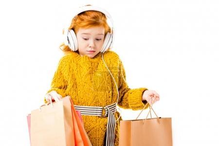 Photo pour Surpris enfant roux cheveux regardant sacs à provisions dans les mains isolées sur blanc - image libre de droit