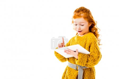Photo for Redhead kid showing idea gesture and looking at tablet isolated on white - Royalty Free Image