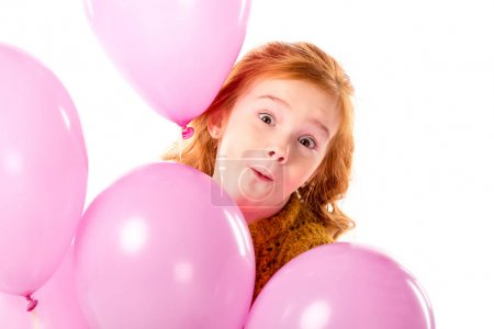Photo for Grimacing red hair child standing with bundle of pink balloons isolated on white - Royalty Free Image