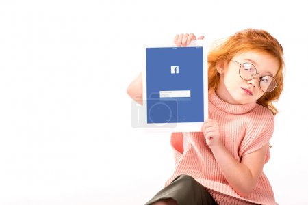 redhead kid sitting and showing loaded facebook page on tablet isolated on white