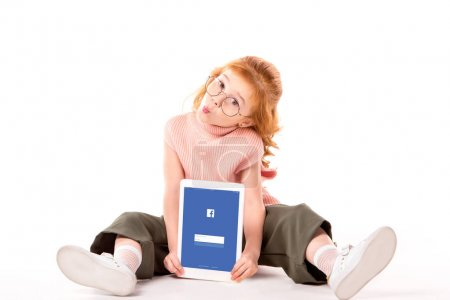red hair child sitting and holding tablet with loaded facebook page on white