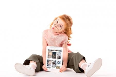 red hair child sitting and holding tablet with loaded pinterest page on white