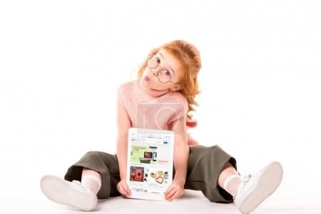 red hair child sitting and holding tablet with loaded ebay page on white