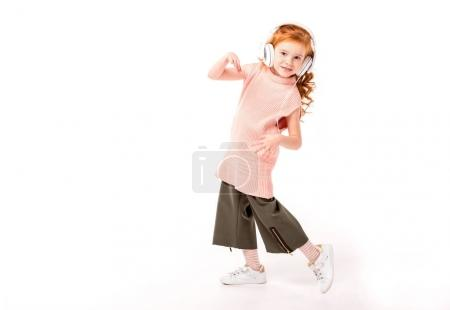 red hair kid in headphones dancing and looking at camera on white