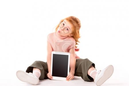 Photo for Kid with ginger hair sitting and showing tablet on white - Royalty Free Image