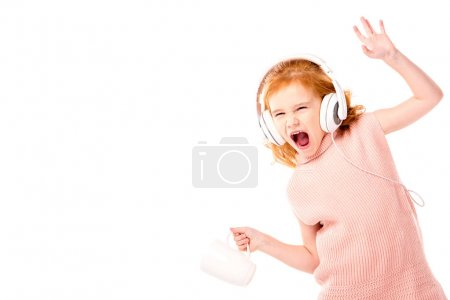 Photo for Red hair kid in headphones screaming and dancing with cup isolated on white - Royalty Free Image