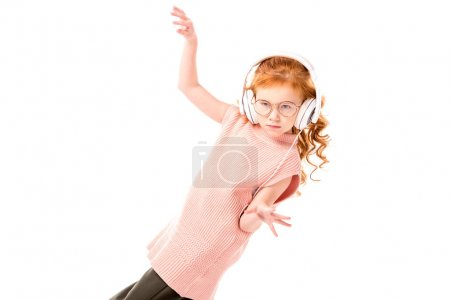 red hair kid listening music in headphones and dancing isolated on white