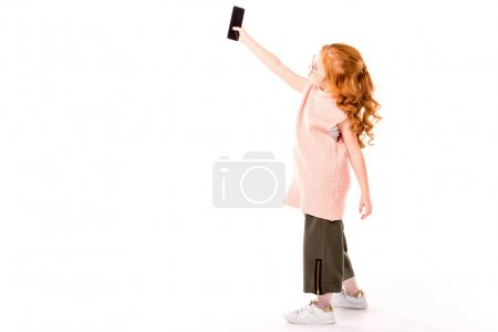 Photo for Redhead kid taking selfie with smartphone on white - Royalty Free Image