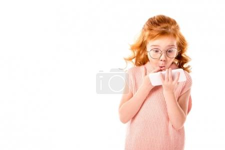 Photo for Surprised kid with ginger hair looking at smartphone isolated on white - Royalty Free Image