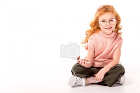 Photo for Kid with ginger hair sitting and holding smartphone on white - Royalty Free Image