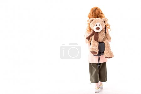 rear view of red hair kid standing with teddy bear on back isolated on white