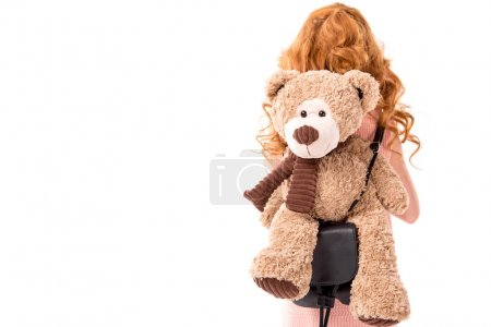 Photo for Rear view of red hair kid with teddy bear isolated on white - Royalty Free Image