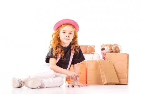 Photo pour Roux cheveu enfant jouer avec shopping voiture jouet sur blanc - image libre de droit