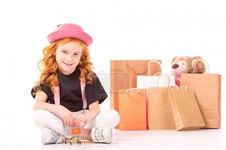 Photo pour Sourire d'enfant assis avec shopping jouet voiture sur blanc - image libre de droit