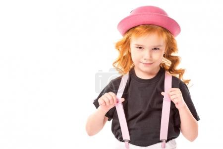funny red hair kid holding pink suspenders isolated on white