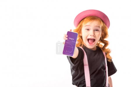 stylish kid in pink hat and suspenders showing smartphone with instagram page isolated on white