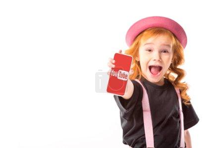 Photo pour Kid chic en chapeau rose et bretelles montrant smartphone avec youtube page isolé sur blanc - image libre de droit