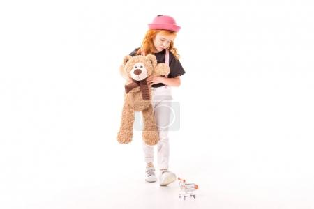 Photo for Upset kid holding teddy bear and looking at shopping car toy on white - Royalty Free Image