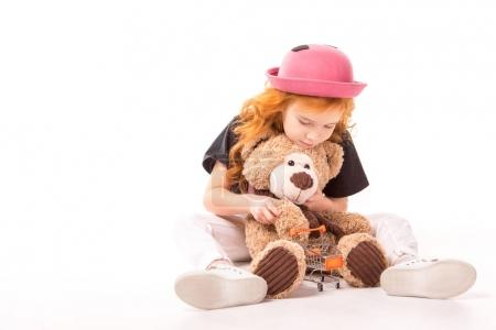 kid playing with teddy bear and shopping car toy on white