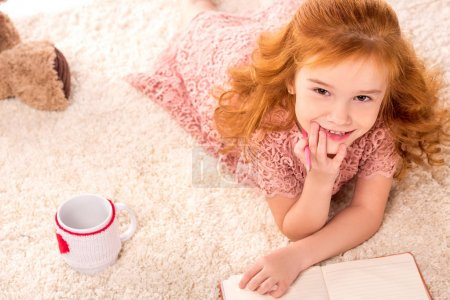 Photo for Overhead view of dreamy redhead kid lying on fluffy carpet - Royalty Free Image