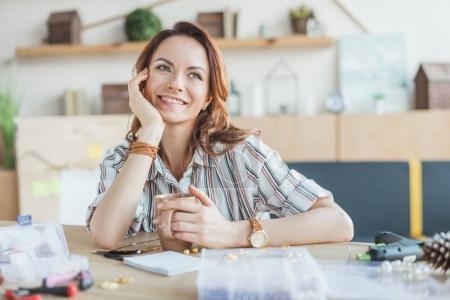 Photo pour Rêveuse jeune femme avec une tasse de café dans l'atelier de la main - image libre de droit