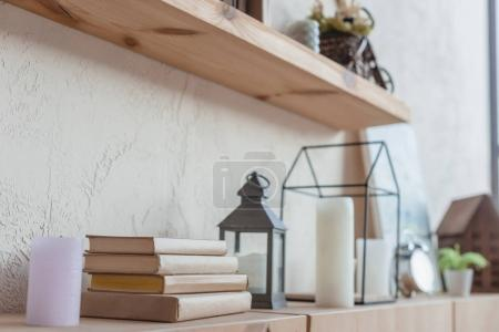close-up shot of bookshelf with beautiful decorations and stack of books