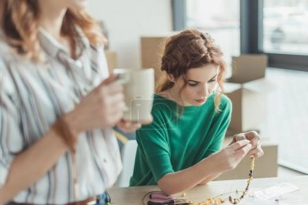 Photo for Concentrated young woman making accessories in workshop while colleague drinking coffee on foreground - Royalty Free Image