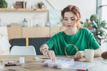 Photo for Young woman making necklaces in handmade workshop - Royalty Free Image