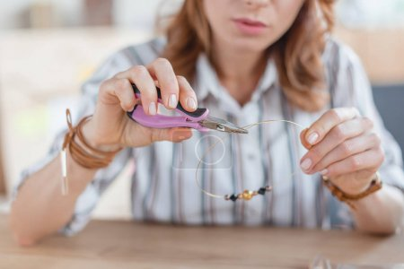 Photo for Young woman making necklace with linesman pliers in workshop - Royalty Free Image