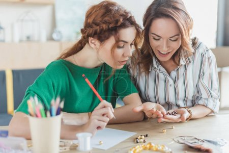Photo for Young women working with beads at handmade accessories workshop - Royalty Free Image