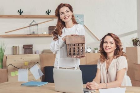 Photo pour Jeunes agents immobiliers sur lieu de travail avec le modèle de maison en bois - image libre de droit