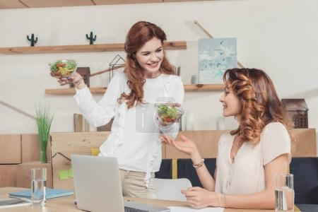young businesswoman sharing healthy salad to colleague