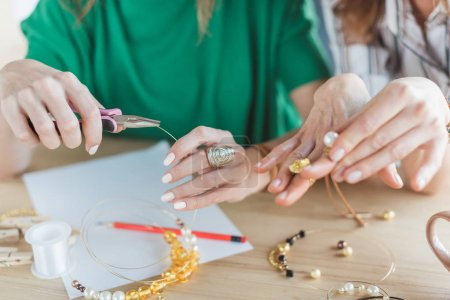 cropped shot of women making accessories of beads