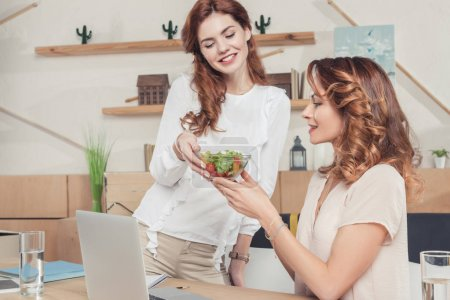 young businesswoman giving healthy salad to colleague