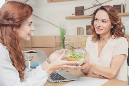 beautiful young coworkers sharing healthy salad at office