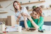 heureux jeunes femmes fabrication d'accessoires à l'atelier