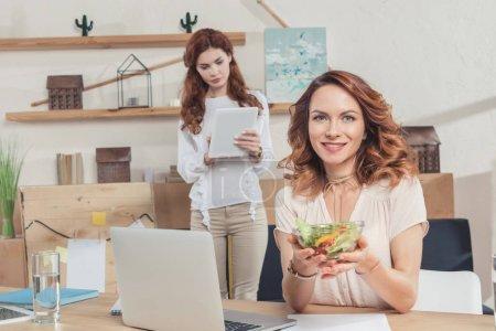 jeune gérante tenant bol de salade sur lieu de travail et en regardant la caméra tandis que son collègue à l'aide de tablette
